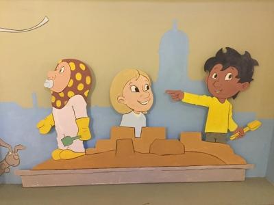 Lasten kaupungin seinäkuvitusta, lapsia hiekkalaatikolla.