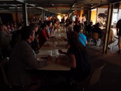 Paljon ihmisiä istuu pitkien pöytien ääressä tehdasmaisessa tilassa