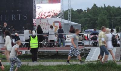 Katsomokorokkeella väkeä, taustalla lava, jolla taustalakana