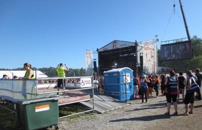 Katsomokoroke, jolla järjestyksenvalvojia, taustalla lava, vieressä wc ja ihmisiä, joilla on sininen liivi yllään