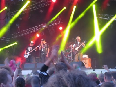 Neljä miestä lavalla, punaisia ja vihreitä valoja