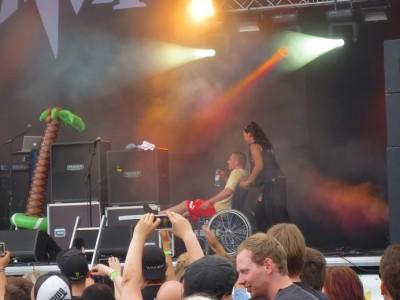 Nainen työntää miestä pyörätuolissa lavalla, etualalla yleisöä. Lavalla vahvistimia ja muovinen palmu.